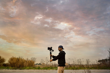 Caucasian videographer filming with cinema gimbal video dslr at sunset , professional video, videographer in event. Cinema lens on gimbal. Long shot