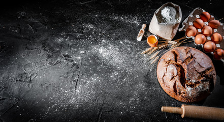 Baked bread, bread roll and flour on black chalkboard. Rural kitchen or bakery - background with free text space