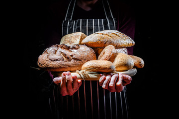 A man in an apron holds many kinds of freshly baked bread