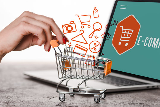 cropped view of woman holding toy shopping cart near laptop and illustration on white, e-commerce concept