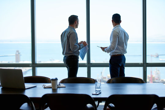 Business colleagues looking out over the ocean from a boardroom
