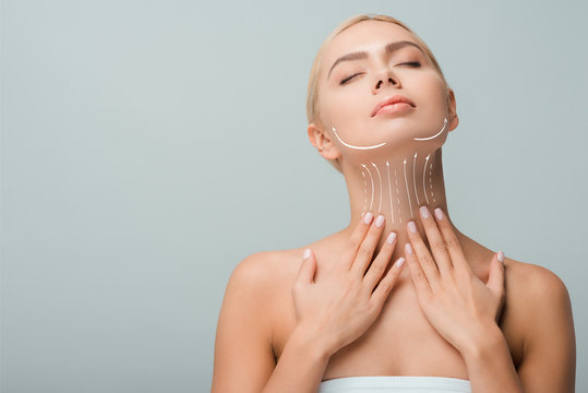 beautiful woman touching neck with lifting marks isolated on grey