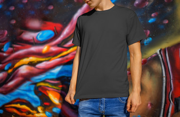 Mockup of empty clothes on a young guy in blue jeans on a background of a wall with graffiti. Wall mural