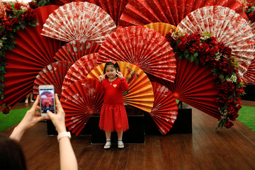 A girl poses for pictures near Lunar New Year decoration at a shopping mall in Jakarta