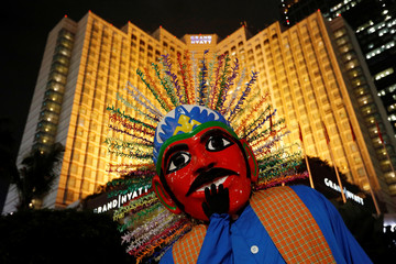 """A traditional large puppet figure called """"Ondel-Ondel"""" is pictured as it performs on the sidewalk in Jakarta"""