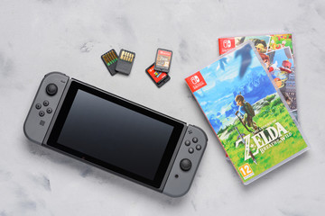 Nintendo Switch gaming console with popular Zelda and Mario games and game cards flat lay on table. Illustrative editorial.