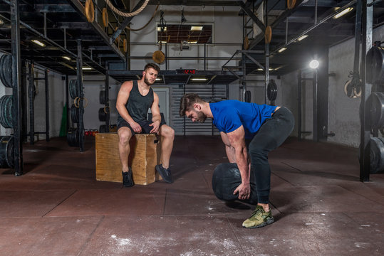 Young muscular sweaty fit instructor or coach man helping veteran man with scars on his skin in rehabilitation process training and workout in the gym with sandbag and other equipment selective focus