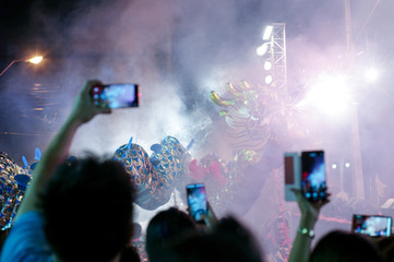 Blurred crowd of people hold the mobile phone recording the motion blurred dragon dancing with firework in background
