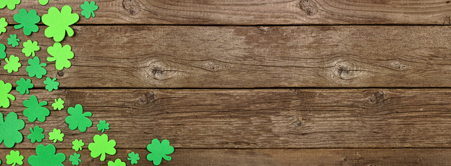 Wall Mural - St Patricks Day banner with corner border of shamrock decorations. Top view over an old rustic wood background. Copy space.