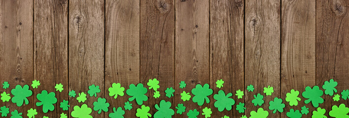 St Patricks Day banner with border border of shamrock decorations. Above view over an old rustic wood background. Copy space.