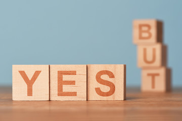 Yes versus but wooden cubes infront of blue background