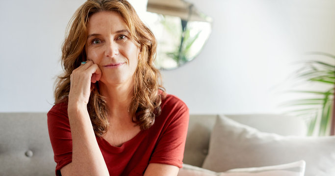 Mature woman smiling contently while relaxing on her sofa