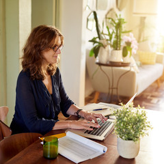 Printed kitchen splashbacks Bonsai Smiling mature female entrepreneur working on a laptop at home