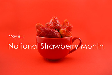 National Strawberry Month. Fresh juicy Strawberry picture. May is Strawberry Month. Strawberries in a red mug stock images. Strawberries on a red background. Red cup with strawberries