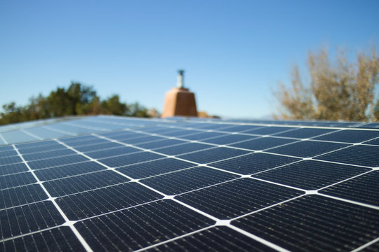 Close shot of a solar panel installation on a rooftop, in horizontal format