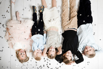 Group picture of five children lying on the floor upside down covered by  Christmas confetti
