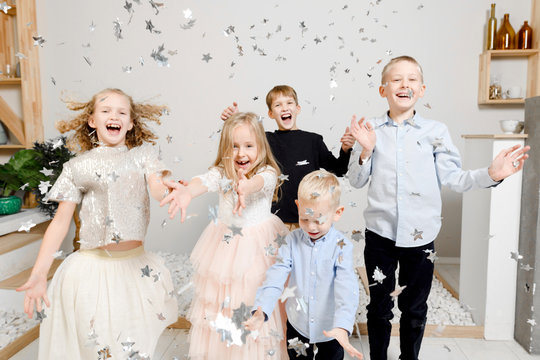 Group picture of five children having fun with Christmas confetti