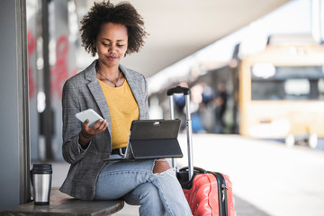 Young businesswoman using tablet and smartphone at the train station