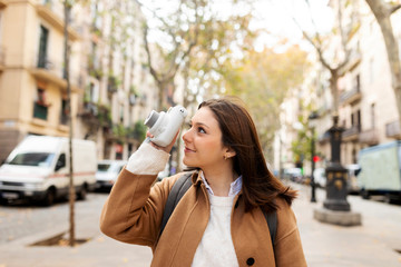 Young woman taking pictures in the city, Barcelona, Spain