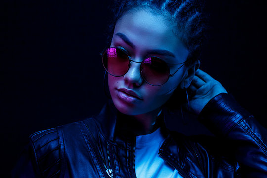 portrait of an African American young woman in sunglasses isolated on a black background in neon light