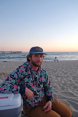 Man Wearing a Cap with Beard and Curly Hair sitting on Beach at Sunset