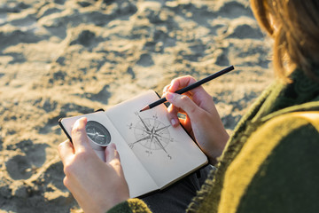 Young woman is drawing a compass in a notebook. Lifestyle, travel