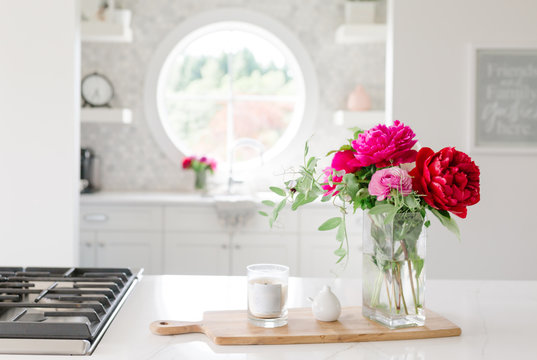 Flowers in a white kitchen  with candle