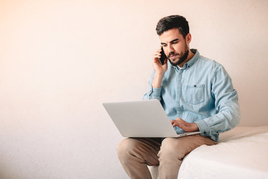 Man talking on smart phone while using laptop computer at home