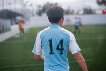 Teenage boy playing indoor soccer wearing light blue jersey number 14