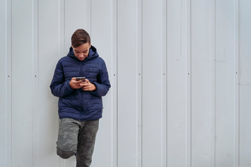 Teen with mobile phone on a white wall