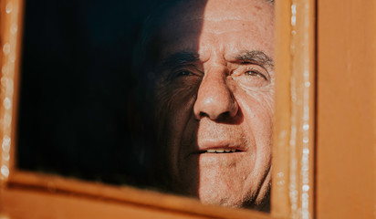 Mature man looking through the window.