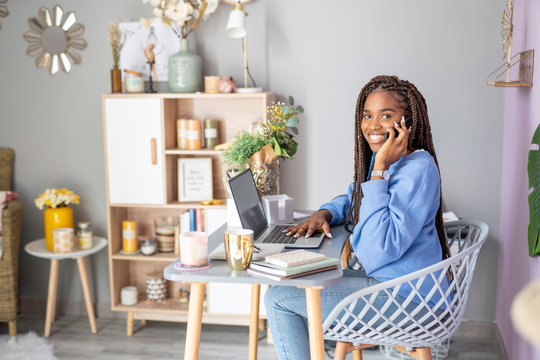 Businesswoman working and talking on her mobile phone at home