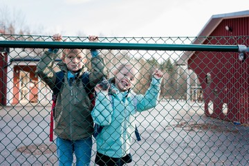 siblings looking through a school fence smiling at their dad