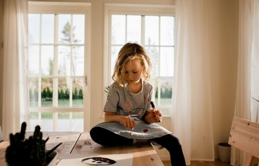 young girl drawing on her hand and face at home