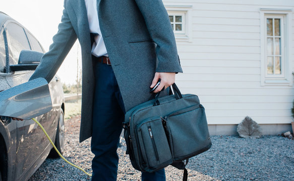 man unplugging electric car holding his work bag leaving home