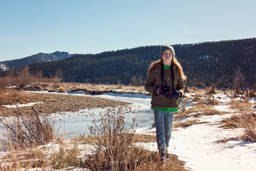 Young Red Hair Girl With Camera Exploring in the Rocky Mountains