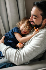 Smiling dad with beard cuddling with happy 4 yr old daughter
