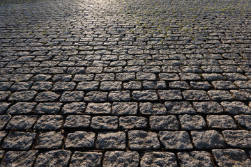 View of a fragment of a square covered with stone pavement. Gray rectangular stones are located regularly. There is reflected light on the surface. Background. Texture. Fototapete