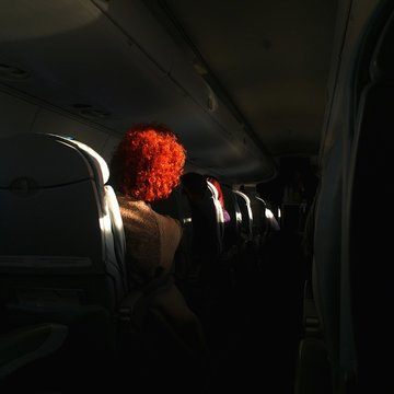 Rear View Of Mature Woman Traveling In Airplane
