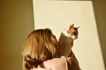 Low Angle View Of Woman With Cat Against Wall