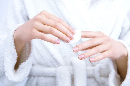 Closeup female hands are holding white cotton cosmetic sponge. Young woman is  erasing polish from nails with remover liquid. Girl is doing manicure at home. Personal hygiene and care concept.