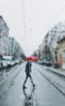 Person With Umbrella Walking On Road Seen Through Wet Window During Rainy Season
