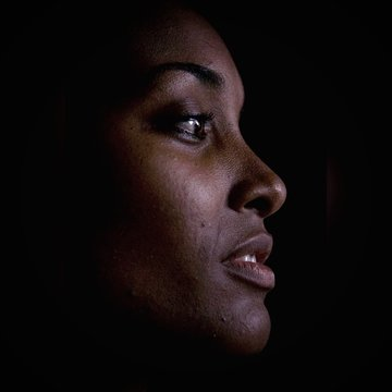 Close-Up Of Mid Adult Woman Against Black Background