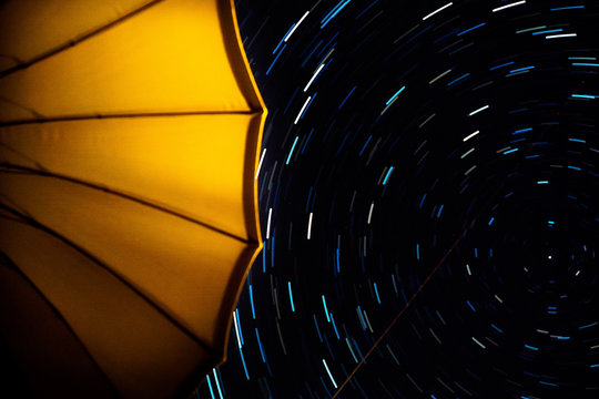 Low Angle View Of Yellow Umbrella Against Star Field At Night