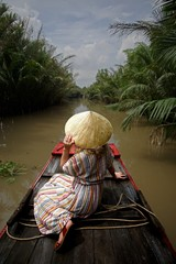 Rear View Of Woman Wearing Asian Style Conical Hat While Sitting On Boat In Lake