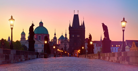 Fotomurales - Charles Bridge in the morning, silhouette of Bridge Tower and saint sculptures with street lights in Prague, Czech Republic
