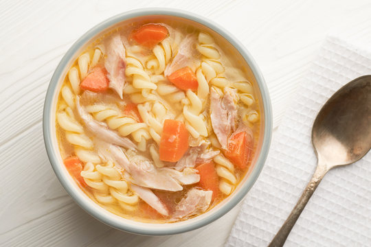 Top view close up of a bowl of chicken noodle soup with spoon on a white wooden background