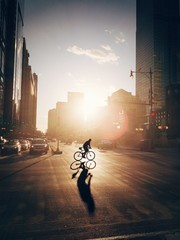 Silhouette Person Cycling On Street During Sunset