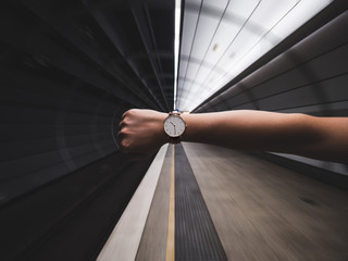 Cropped Image Of Woman Hand Showing Wristwatch At Subway Station