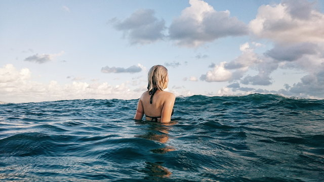 REAR VIEW OF WOMAN SWIMMING IN OCEAN